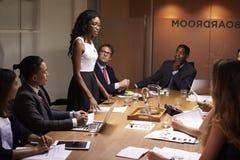 Svarta affärskvinnaställningar som tilltalar kollegor på mötet royaltyfri fotografi