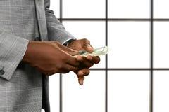 Svarta affärsmans händer som rymmer pengar Royaltyfria Bilder