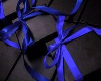 Svarta askar för packande gåvor med blåa pilbågar Royaltyfri Foto