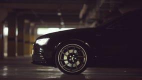 Svarta Audi lämnar parkeringsplatsen med dess ljus stock video