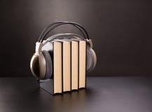 Svarta böcker och hörlurar Arkivfoto