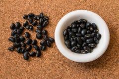 Svarta bönor i maträtten på korken stiger ombord arkivbild