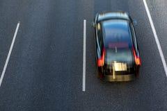 Svarta bilkörningar fastar i huvudvägen vid den högra gränden på solnedgången Utrymme för bästa sikt och kopieringsi den vänstra  Arkivfoton