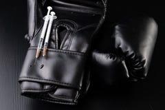 Svarta boxas handskar, stetoskop och injektionsspruta på tabellen Utbildningstillbehör royaltyfri fotografi