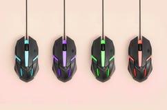 Svarta datormouses hänger på pastellfärgad persikabakgrund royaltyfri bild