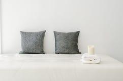 Svarta dekorativa kuddar, stearinljus och vithandduk Arkivfoto