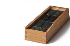 Svarta dominobrickor i en tr?ask som isoleras p? en vit bakgrund kopiera avst?nd royaltyfri bild