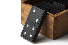 Svarta dominobrickor i en tr?ask som isoleras p? en vit bakgrund kopiera avst?nd royaltyfria bilder