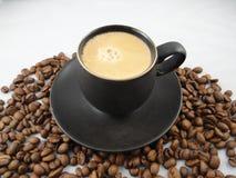 Svarta espressokopp- och kaffebönor arkivfoton