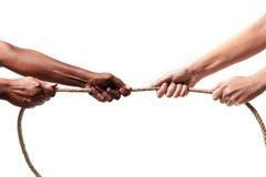 Svarta etnicitetarmar med det dragande repet för händer mot den vita Caucasian lopppersonen i stopprasism och xenofobibegrepp Royaltyfria Bilder
