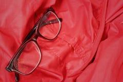 Svarta exponeringsglas på en bakgrund av rött Arkivfoto