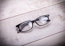 Svarta exponeringsglas på wood bakgrund Arkivfoton
