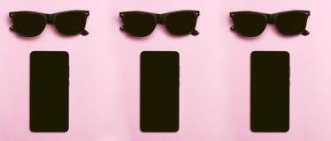 svarta exponeringsglas svart telefon Rosa bakgrund Den svarta telefonen och exponeringsglas ligger på en rosa bakgrund Royaltyfri Foto