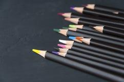 Svarta färgrika blyertspennor på svart bakgrund Mörk version arkivfoto