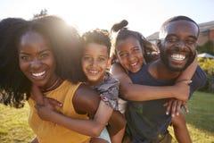 Svarta föräldrar som piggybacking upp deras unga ungar, slut arkivbilder