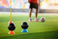 Svarta fotbollbollar på markörkottar på grön konstgjord torva med lagledaren eller fotbollspelaren för utbildning arkivfoto