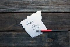 Svarta fredag som är skriftlig på ett papper Fotografering för Bildbyråer