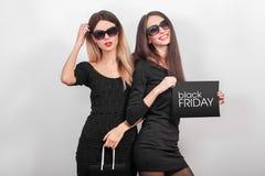 svarta friday försäljning Två unga le kvinnor som visar shoppingpåsen Fotografering för Bildbyråer