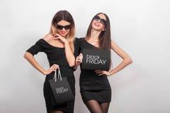 svarta friday försäljning Två unga le kvinnor som visar shoppingpåsen Royaltyfri Fotografi