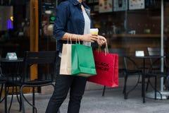 svarta friday Kvinna med kaffekoppen som rymmer shoppingpåsar arkivbild