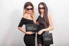 svarta friday Två kvinnor som bär den svarta klänningen och sunglass, med s Arkivbilder