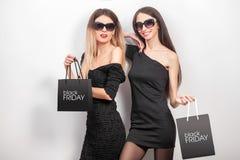 svarta friday Två kvinnor som bär den svarta klänningen och sunglass, med s Royaltyfria Bilder