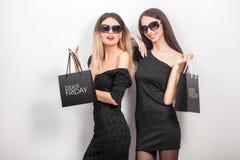 svarta friday Två kvinnor som bär den svarta klänningen och sunglass, med s Royaltyfri Fotografi