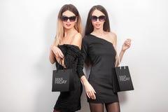 svarta friday Två kvinnor som bär den svarta klänningen och sunglass, med s Royaltyfri Bild