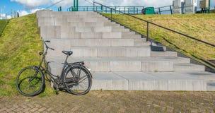 Svarta gamla damer cyklar bredvid en konkret trappuppgång Arkivbild