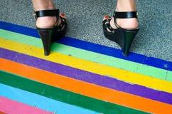 Svarta höga häl som står på regnbågebanden Fotografering för Bildbyråer