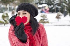 Svarta haired turkiska kvinnor som rymmer en röd hjärta med svarta varma ullhandskar och firar valentin dag Arkivfoton