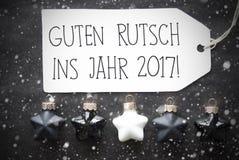 Svarta julbollar, snöflingor, nytt år för Guten Rutsch 2017 hjälpmedel Arkivfoto