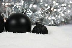 Svarta julstruntsaker som kura ihop sig i snö Royaltyfri Foto