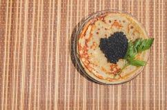 svarta kaviarpannkakor Arkivbild