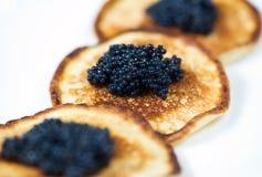 svarta kaviarpannkakor Arkivfoton