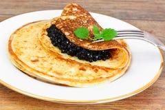 svarta kaviarpannkakor Arkivbilder