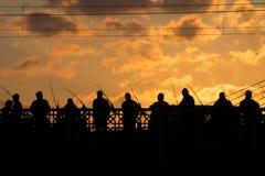 Svarta konturer av fiskare som står på en bro Royaltyfria Bilder