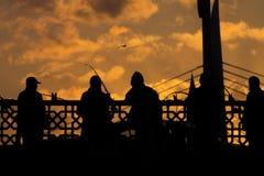 Svarta konturer av fiskare som står på en bro Arkivbild