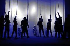 Svarta konturer av folk med rep i deras händer på teatern, skuggalek Arkivfoto