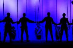 Svarta konturer av folk som rymmer händer på etappen av teatern främsta av repen Royaltyfri Bild