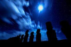 Svarta konturer av stående moais mot stjärnklar blå himmel i E Arkivbild