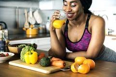 Svarta kvinnan dricker orange fruktsaft royaltyfria bilder