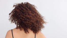 Svarta kvinnan för det blandade loppet med fräknar och lockigt hår i studio på vit poserar till en kamera arkivfilmer