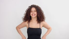 Svarta kvinnan för det blandade loppet med fräknar och lockigt hår i studio på vit poserar till en kamera stock video