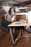 Svarta kvinnan tycker om kopplar av på coffeeshop Arkivbilder