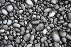 Svarta lavakiselstenar på stranden Royaltyfria Bilder