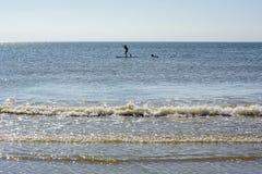 Svarta människor kontur en på bränningen på det blåa vattnet Fotografering för Bildbyråer