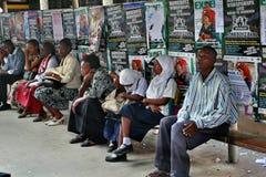 Svarta människor sitter på bänk på bakgrund av affischer Arkivfoto