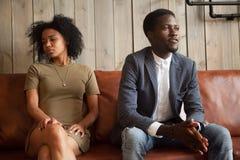 Svarta maker som åt sidan som sitter på soffan inte är klar att kompromissa royaltyfria bilder
