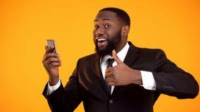 Svarta manliga visande tummarsom tillfredsst?lls med mobil applikationkapacitet, hj?lpmedel fotografering för bildbyråer